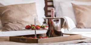 Schaal met champagne op een bed, met aardbeien