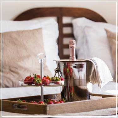 Champagneontbijt op een bed in een huisje